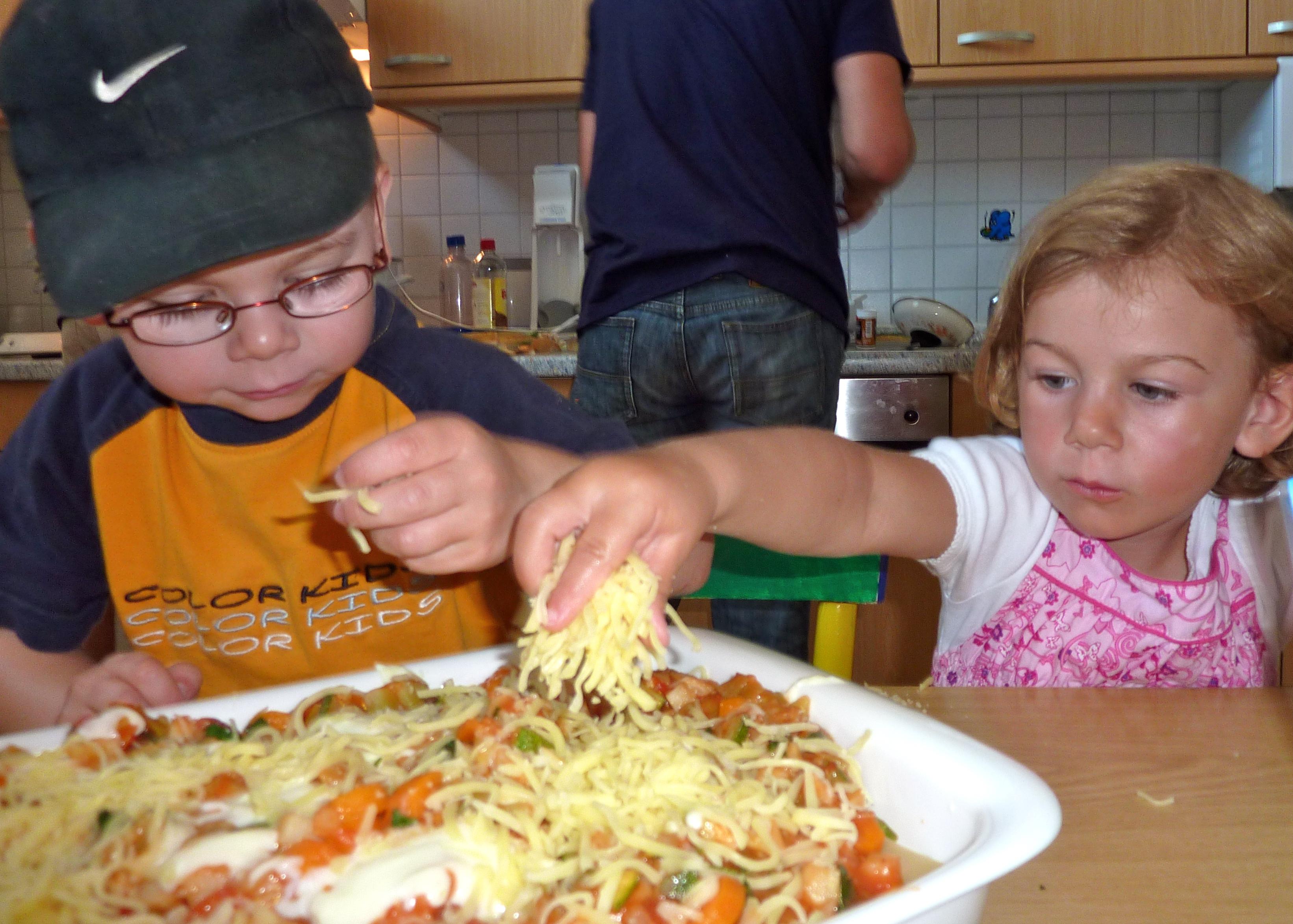 Norderney - Mädchen streut Käse über Gemüselasagne