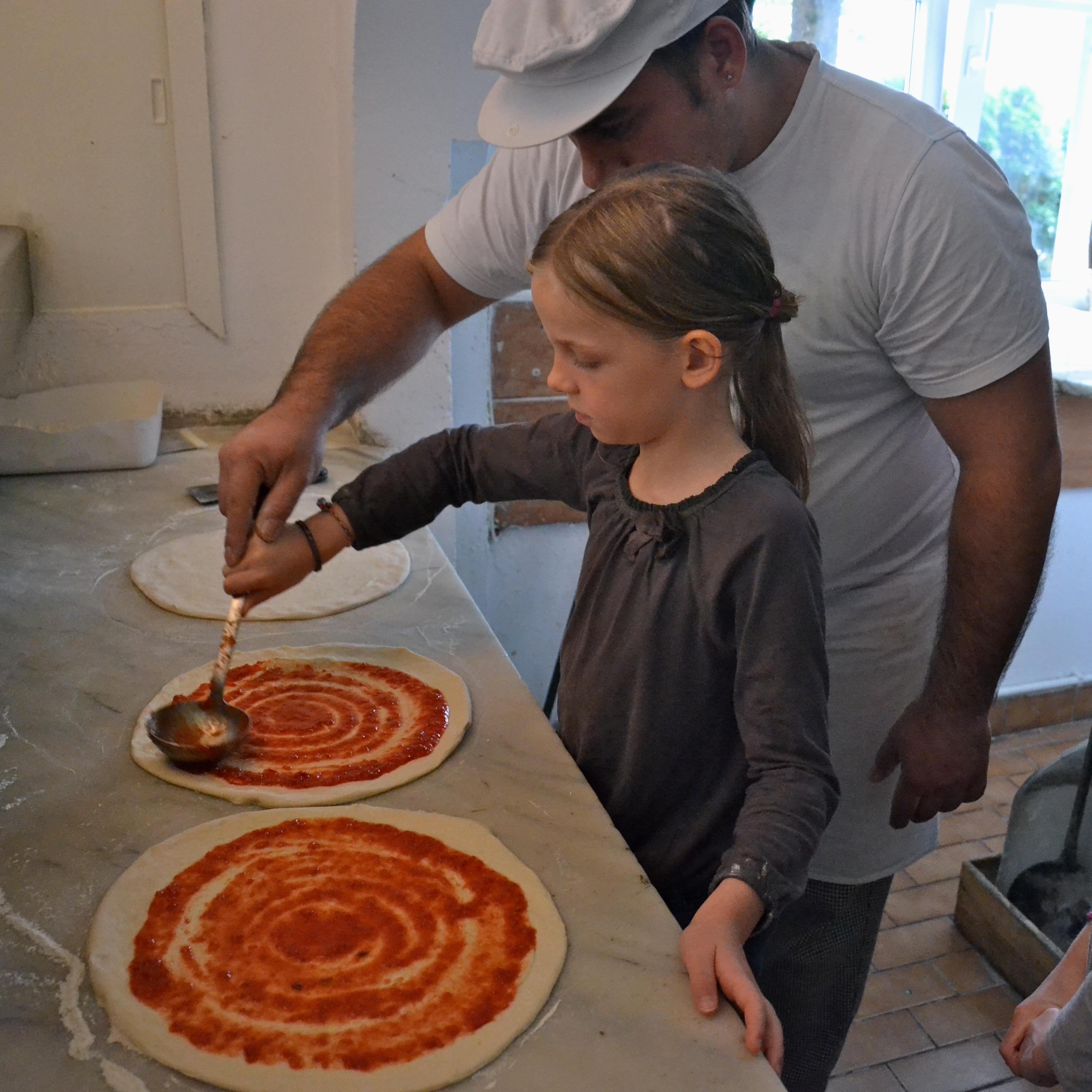 Kinderpizza - Anna bestreicht ihre Pizza mit Tomatensauce