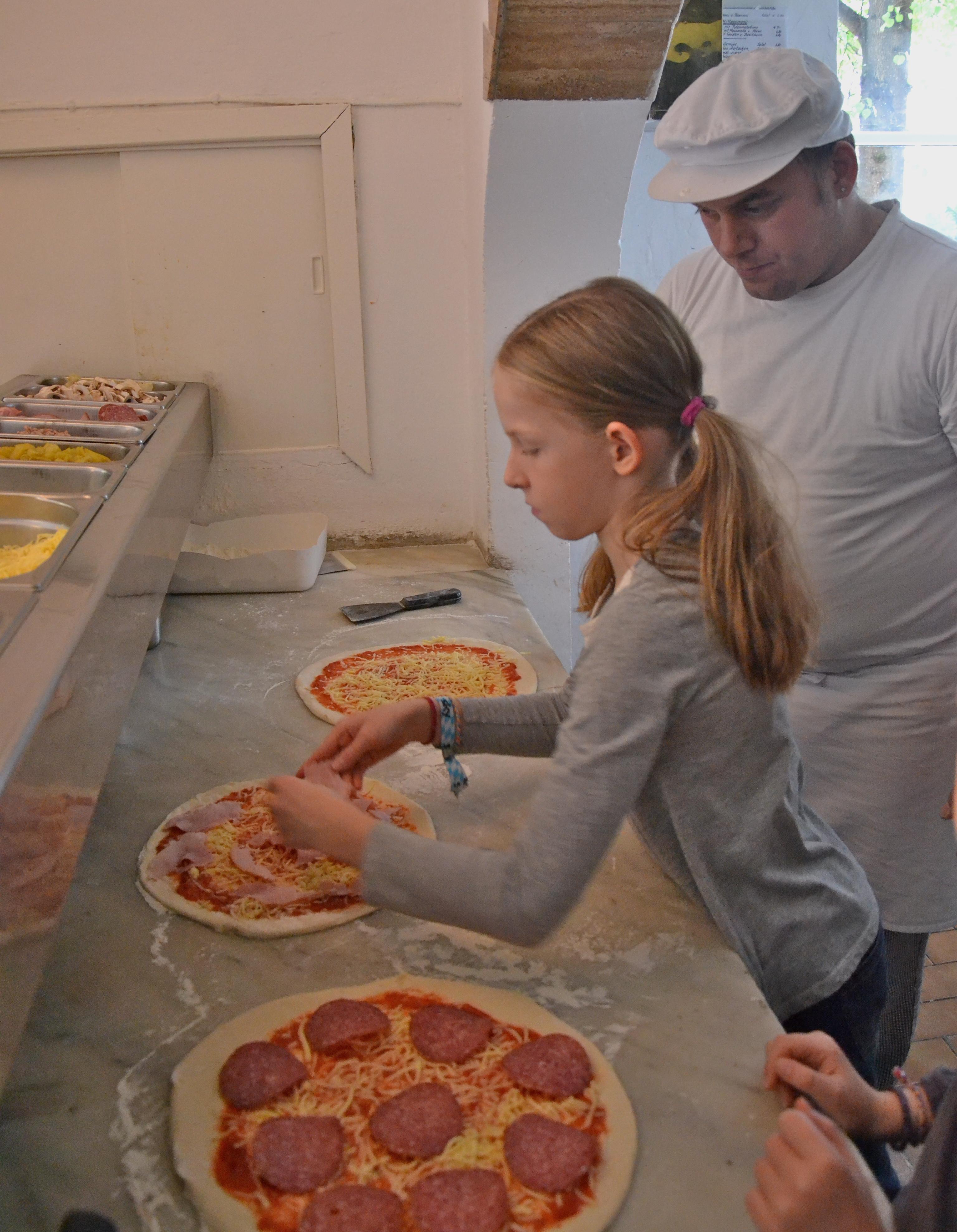 Kinderpizza - Marie legt gekochten Schinken auf ihre Pizza