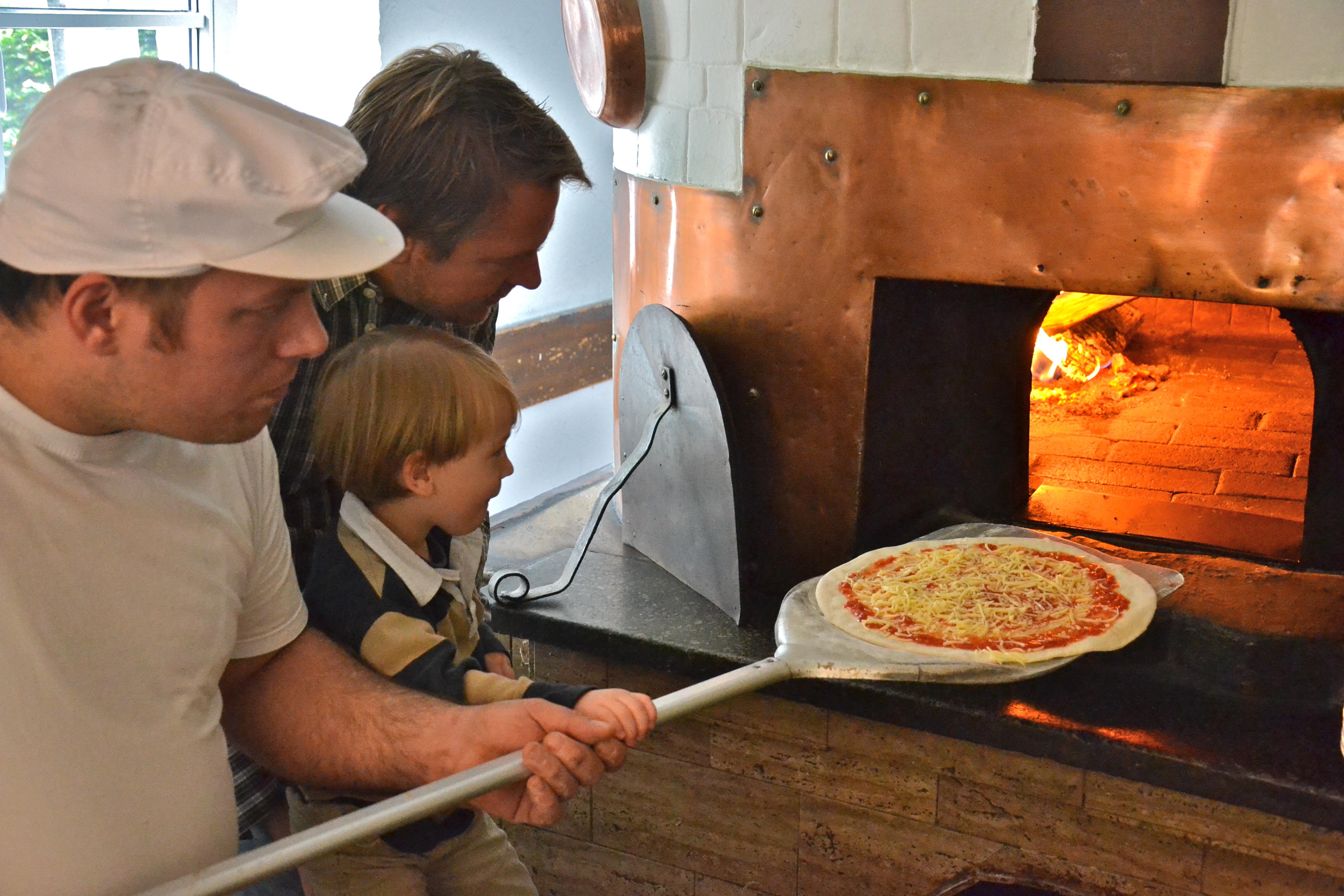 Kinderpizza - Peter schiebt seine Pizza in den Holzofen