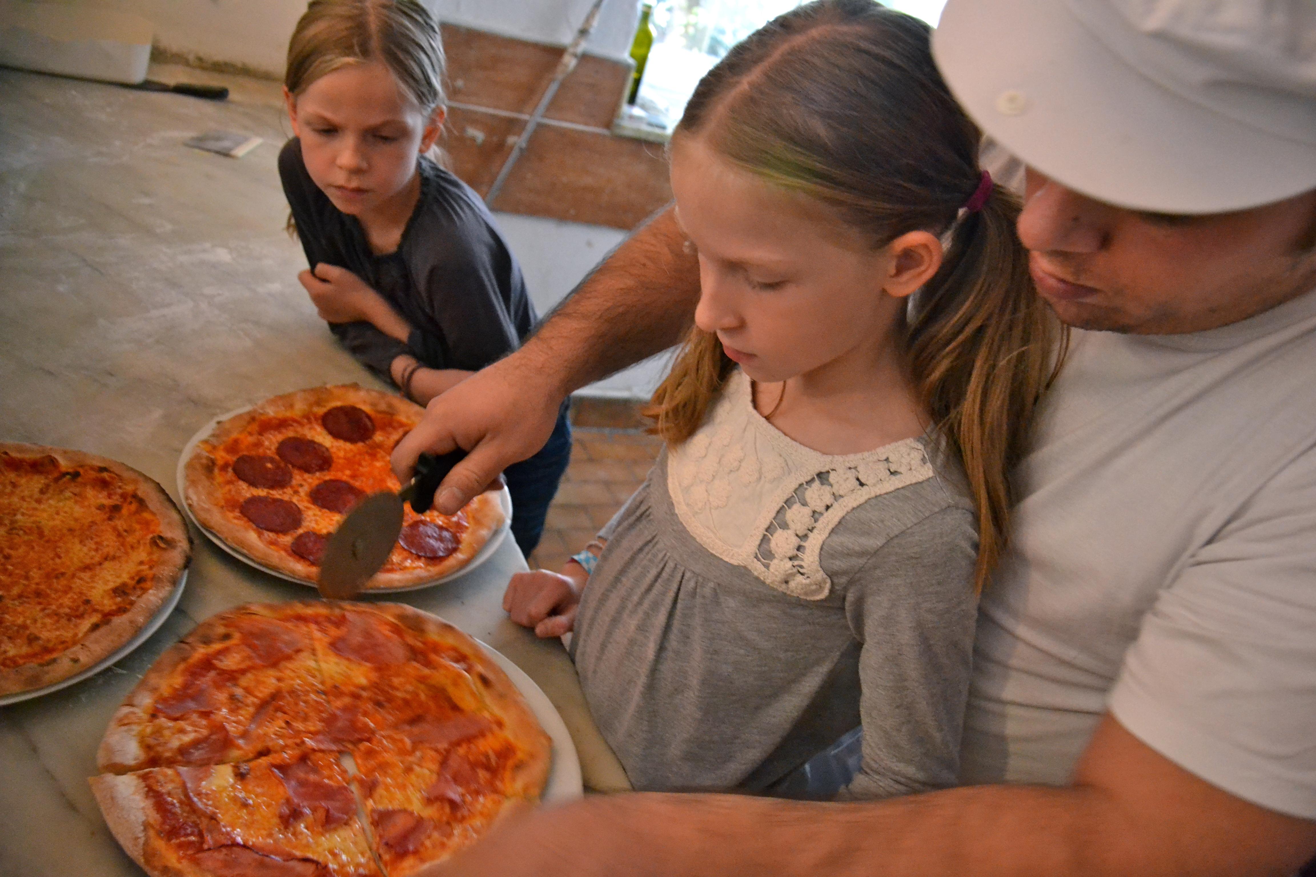 Kinderpizza - Francesco schneidet die Pizza in Stücke