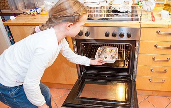 Marie schiebt das Brathähnchen in den Ofen